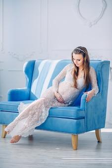 青い椅子に座って、妊娠中の腹を保持している白いレースペニョワールランジェリーの美しい妊娠中の女性