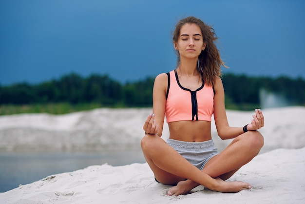 Здоровая женщина практикующих йогу и медитировать на пляже в песке возле голубого облачного неба
