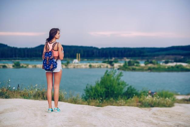 若い美しい日焼けした女性は、バックパックで旅行します。湖の近くを歩きます。