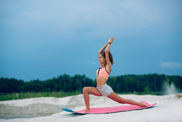 青い曇り空の近くのビーチでヨガの戦士のポーズを練習する若い女性