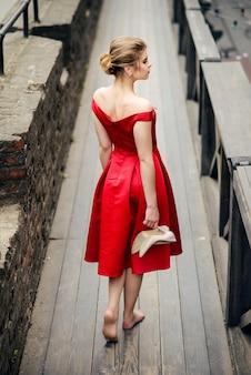 手に木製の橋の上を歩いて素足で彼女の靴を保持している赤いドレスを着た魅力的な美しい女性