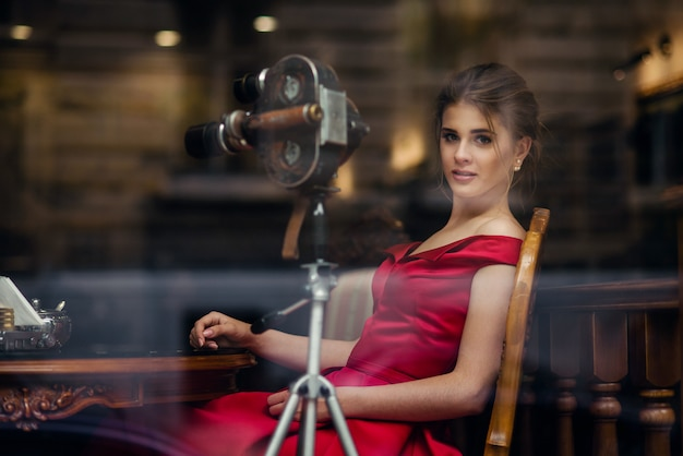 Привлекательная красивая женщина в красном платье сидит на деревянном стуле возле раритетной винтажной камеры