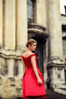 列を持つ歴史的な建物の近くに立っている赤いドレスの魅力的な美しい女性