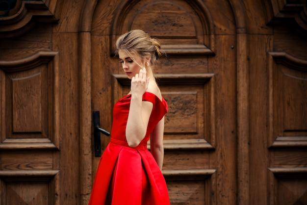 古いヴィンテージの木製のドアの上の街で赤いドレスの魅力的な美しい女性