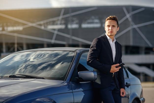 車の近くのスマートフォンで魅力的なハンサムな実業家