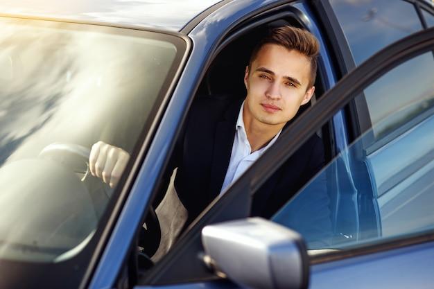 Привлекательный красивый элегантный мужчина в деловом костюме за рулем дорогой машины