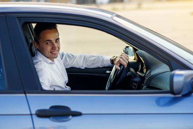高価な車を運転して白いシャツで魅力的なハンサムな笑みを浮かべて男