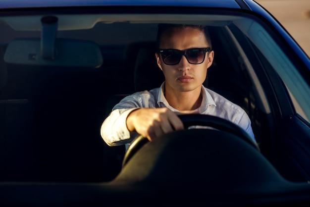 Привлекательный серьезный красавец в белой рубашке и солнцезащитные очки за рулем дорогой машины