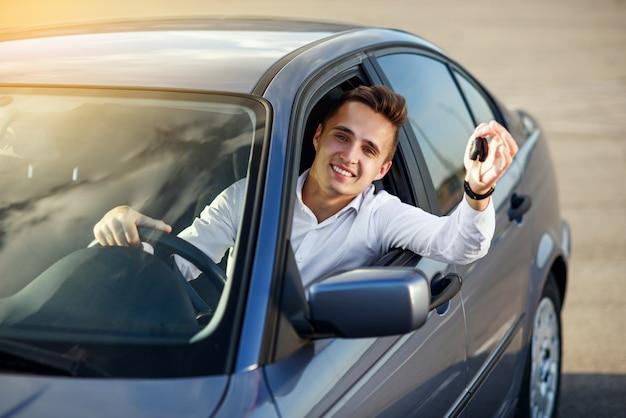 彼の新しい車の中に車のキーを保持している幸せなバイヤー