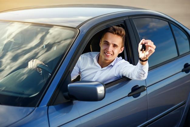 Счастливый покупатель держит ключи от машины внутри своего нового автомобиля
