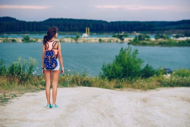 若い美しい日焼けした女性は、バックパックで旅行します。湖の上を歩きます。