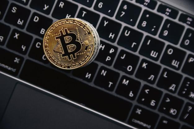 Золотые биткойны на клавиатуре компьютера