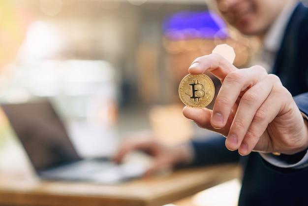 成功した笑顔の実業家は彼の手で金ビットコインを保持しています。