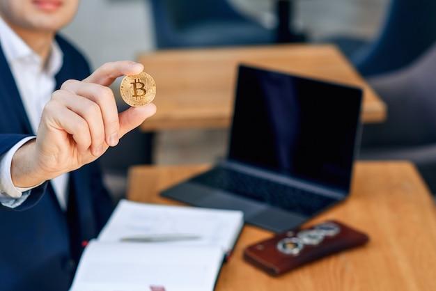 Успешный бизнесмен держит в руке золотую монету биткойн