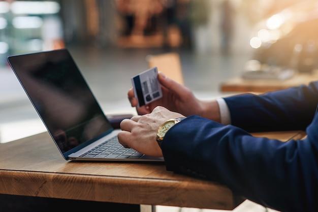 木製のテーブルでカフェに座ってコンピューターのキーボードで数字を入力するクレジットカードを保持している実業家