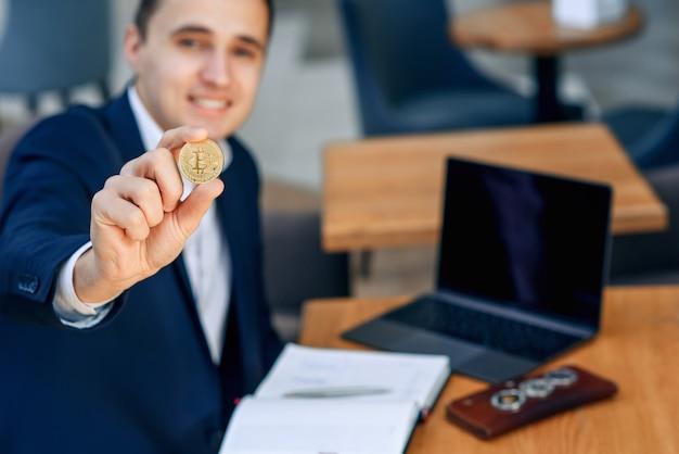 Успешный улыбающийся бизнесмен держит в руке золотую монету биткойн