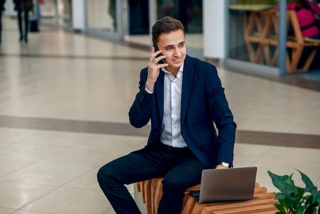 ラップトップに取り組んでいると、ベンチに座っているスマートフォンを話す成功した若い実業家