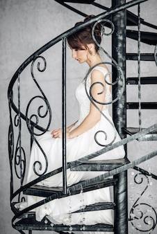 明るいインテリアで鍛造階段の上に座って美しい若い花嫁