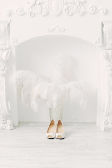 暖炉と白いインテリアのダチョウの羽の上の白い結婚式の靴