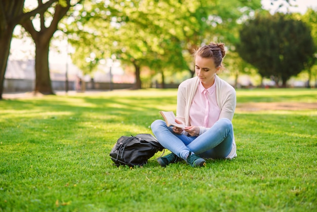 草の上に座って、夏の公園で本を読んで美しい女性