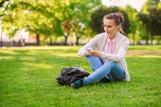 草の上に座って、夏に公園でスマートフォンを使用して美しい女性