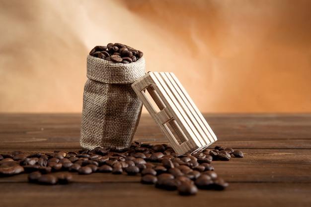 Кофе в зернах в небольшой сумке на деревянном столе