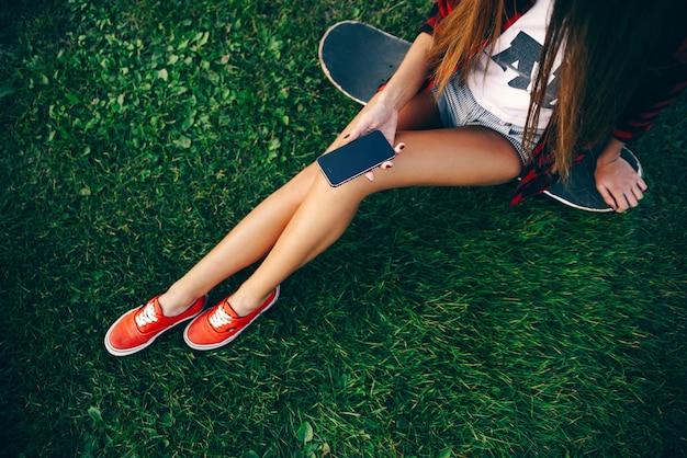 Красивая молодая женщина в белой футболке, красной рубашке, шортах и кроссовках сидит на скейтборде на траве