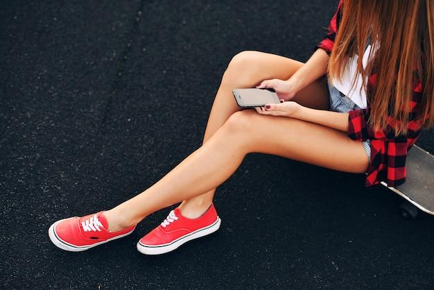 Красивая женщина в белой футболке, красной рубашке, шортах и кроссовках сидит на скейтборде на траве