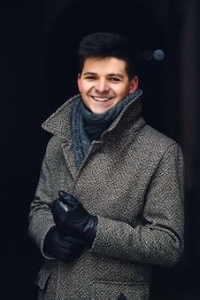 暖かいコートと革手袋でハンサムな笑みを浮かべて若い男
