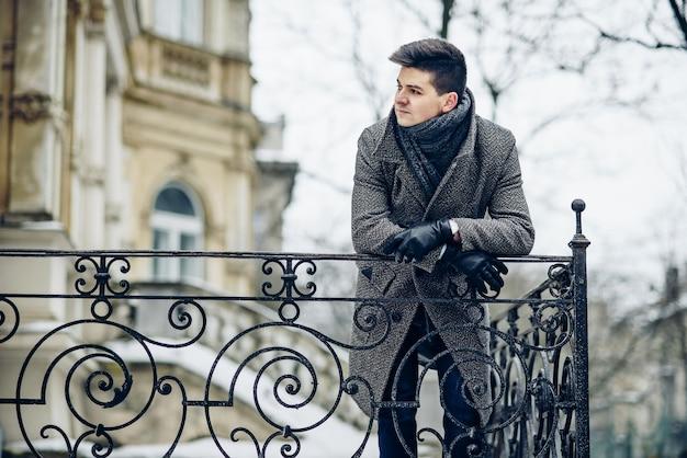 温かみのあるグレーのコートと革手袋のスタイリッシュな若い男が偽造フェンスに寄りかかった