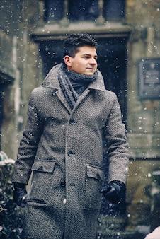 Стильный молодой человек в теплом сером пальто гуляет по улице во время снегопада
