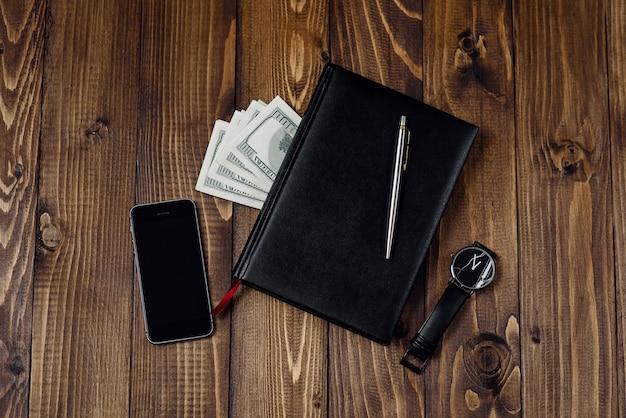 スマートフォン、時計、ペン、ノート、お金の平面図