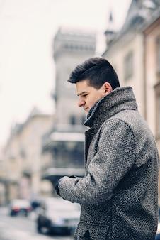 暖かいコートと革手袋でハンサムな男。