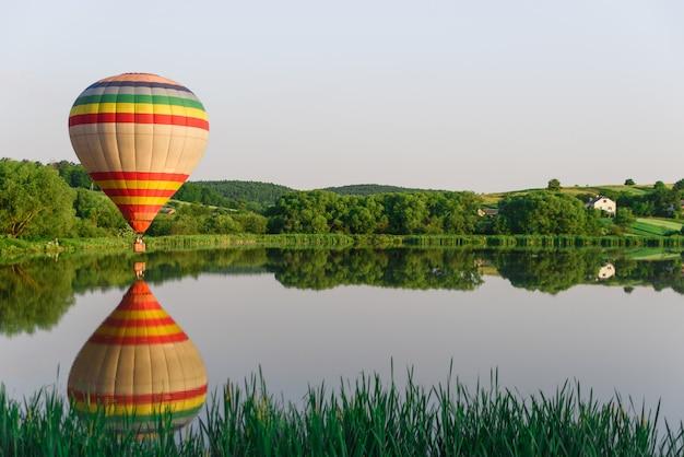 水の近くの湖の上を飛んでいるマルチカラーの熱気球。自然の中でバルーニング。