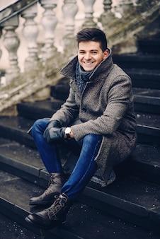 Молодой стильный мужчина в теплом сером пальто и кожаных перчатках сидит на лестнице