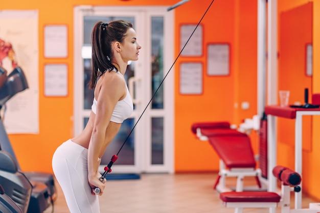 Красивая спортивная женщина с совершенным трицепсом тренировки тела в спортзале