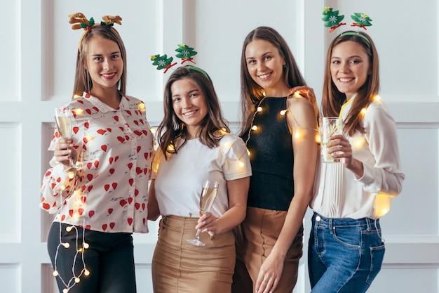 Группа молодых женщин, празднующих рождество, новый год