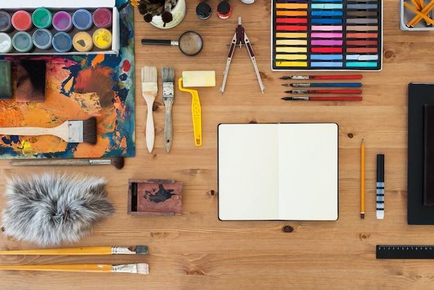 画家職場のトップビュー。描画のためのアートツールを持つアーティストの木製テーブル。