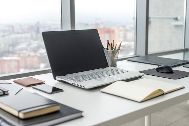 Рабочее место с ноутбуком удобный рабочий стол в офисных окнах и с видом на город.