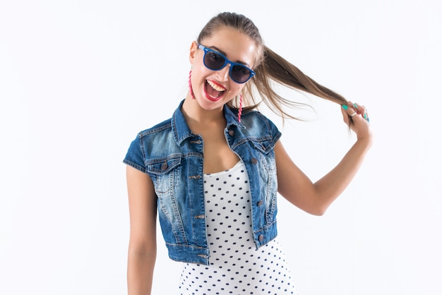 Молодая счастливая девушка смеется, держа ее за волосы, имитируя прически хвосты, носить солнцезащитные очки и модный наряд.
