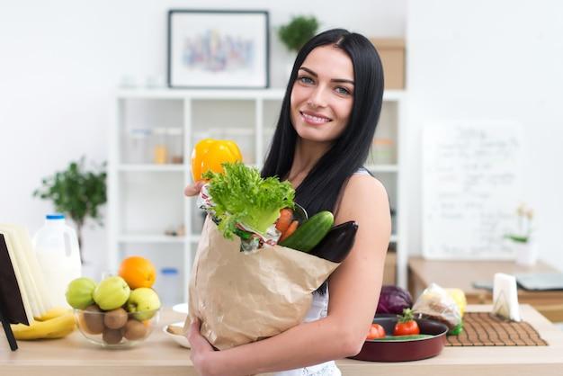 紙袋いっぱいの新鮮な野菜を保持している女性のクローズアップの肖像画。食料品店で幸せな笑みを浮かべて女性ベジタリアン。