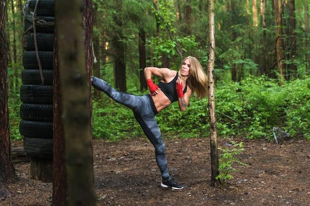 Подходит девушка бить высокой ногой боковой удар работает на открытом воздухе. женщина боец тренируется, занимается кикбоксингом, тренирует боевые искусства