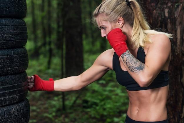 Портрет девушки боксер делает апперкот пинком, разработка на открытом воздухе.