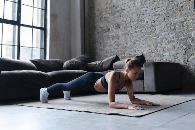カーペットの上板張り運動をして自宅でワークアウトスポーツウェアを着ている若い女性に合う
