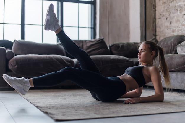 代替脚を上げるとクランチ運動を実行するリビングルームで腹筋運動を行う若いスポーティな女性