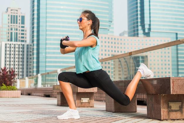 ベンチで片足の突進運動を行うスポーティな女性アスリート。市の路地で屋外ワークアウトフィットの若い女性