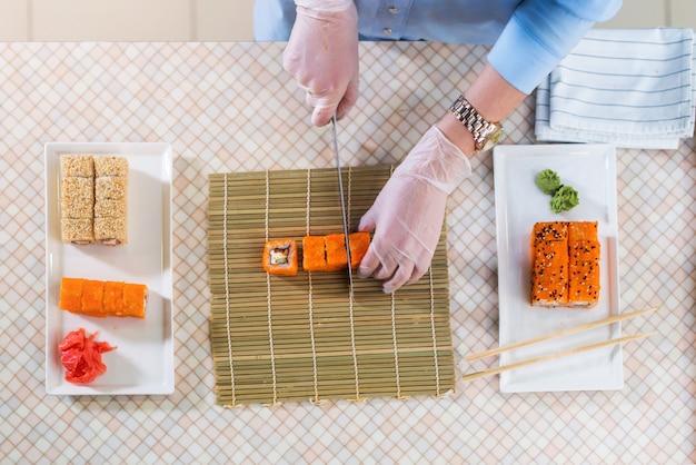 レストランで巻き寿司を作る手袋で働く女性シェフのトップビュー