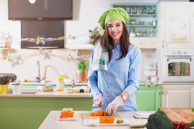 Женщина-повар в шляпе и перчатках от шеф-повара готовит японские суши-роллы