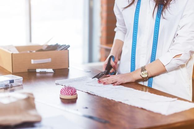縫製工場でテーブルにハサミで布を切るテーラーの手のクローズアップ写真。