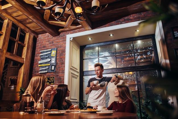 Студенты во время обеденного перерыва пьют кофе, слушая разговор своего друга в модной кофейне